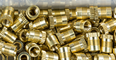 small bronze threaded parts in a box