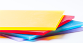 colorful polycarbonate sheets stacked on a white background